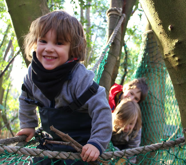 Children climbing outdoors at The Nature Kindergarten